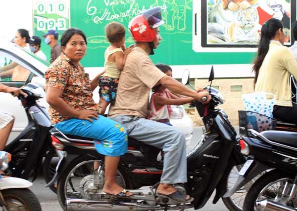 2 adultes et 2 enfants sur une mobylette