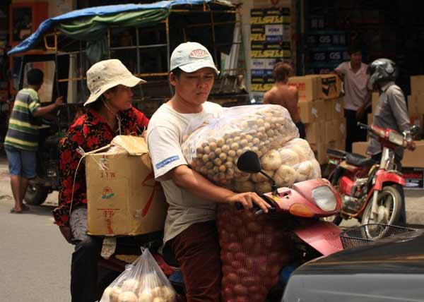 Deux sur une mobylette avec des provisions