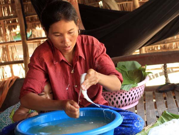 Femme rinçant les nouilles de riz